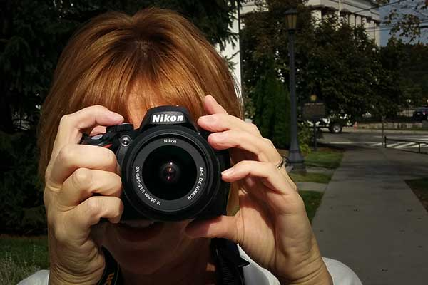 Image of woman holding a Nikon camera